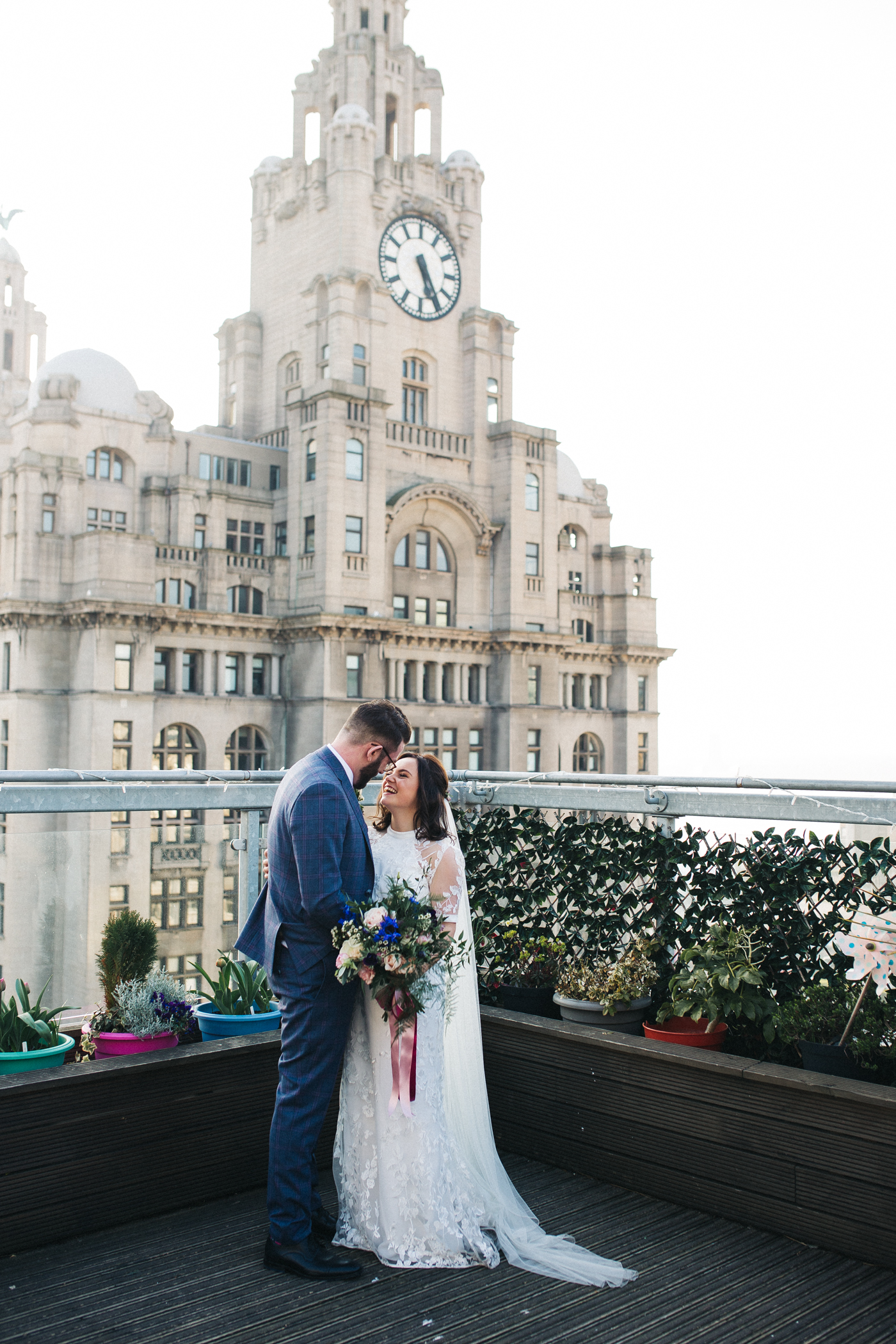 the bride and groom stand smiling to each other in front of the liver building. ceremony at st georges hall liverpool, oh me oh my wedding reception, north west wedding photographer