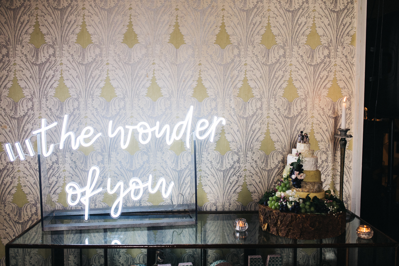 the cheese wedding cake on a table with a neon sign that reads ' the wonder of you'. ceremony at st georges hall liverpool, oh me oh my wedding reception, north west wedding photographer