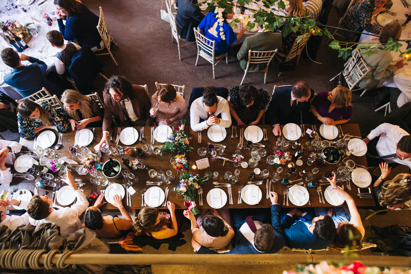 a birds eye shot of guests sitting at a long table. ceremony at st georges hall liverpool, oh me oh my wedding reception, north west wedding photographer