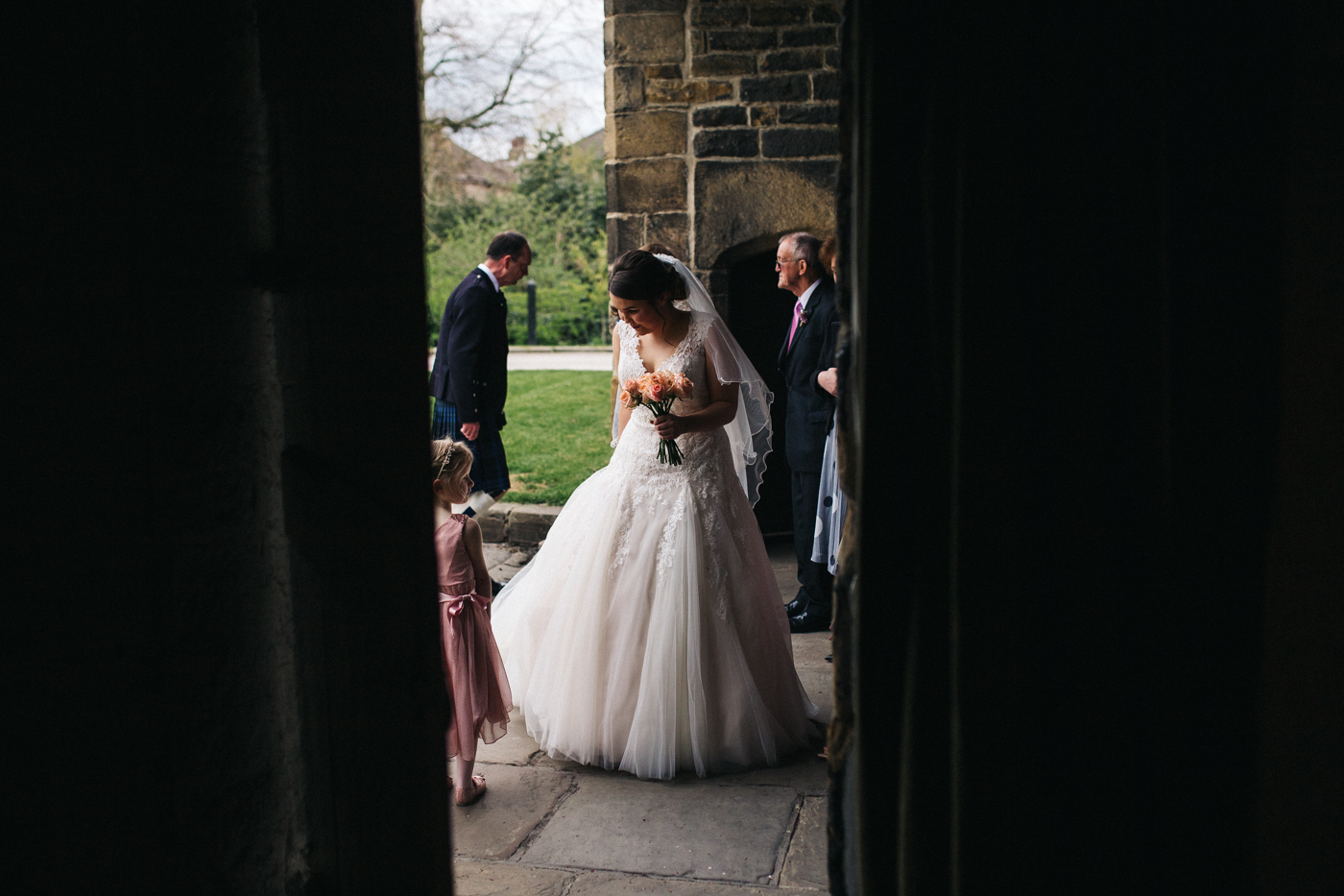 the bride stands outside before entering the ceremony. spring barn wedding at east riddlesden hall keighley west yorkshire wedding photographer