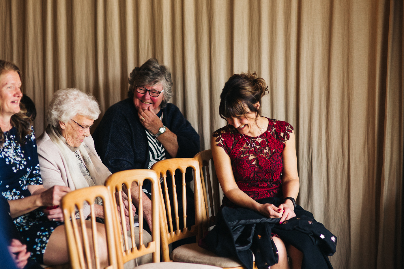 the brides mum laughs in her seat at the ceremony. spring barn wedding at east riddlesden hall keighley west yorkshire wedding photographer