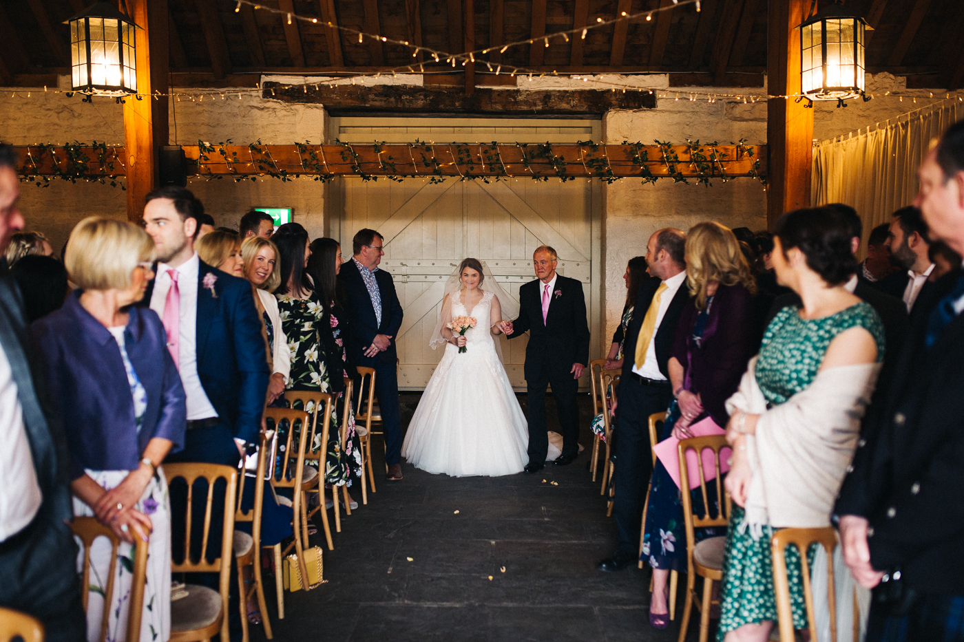 the bride walks down the aisle with her grandad. spring barn wedding at east riddlesden hall keighley west yorkshire wedding photographer