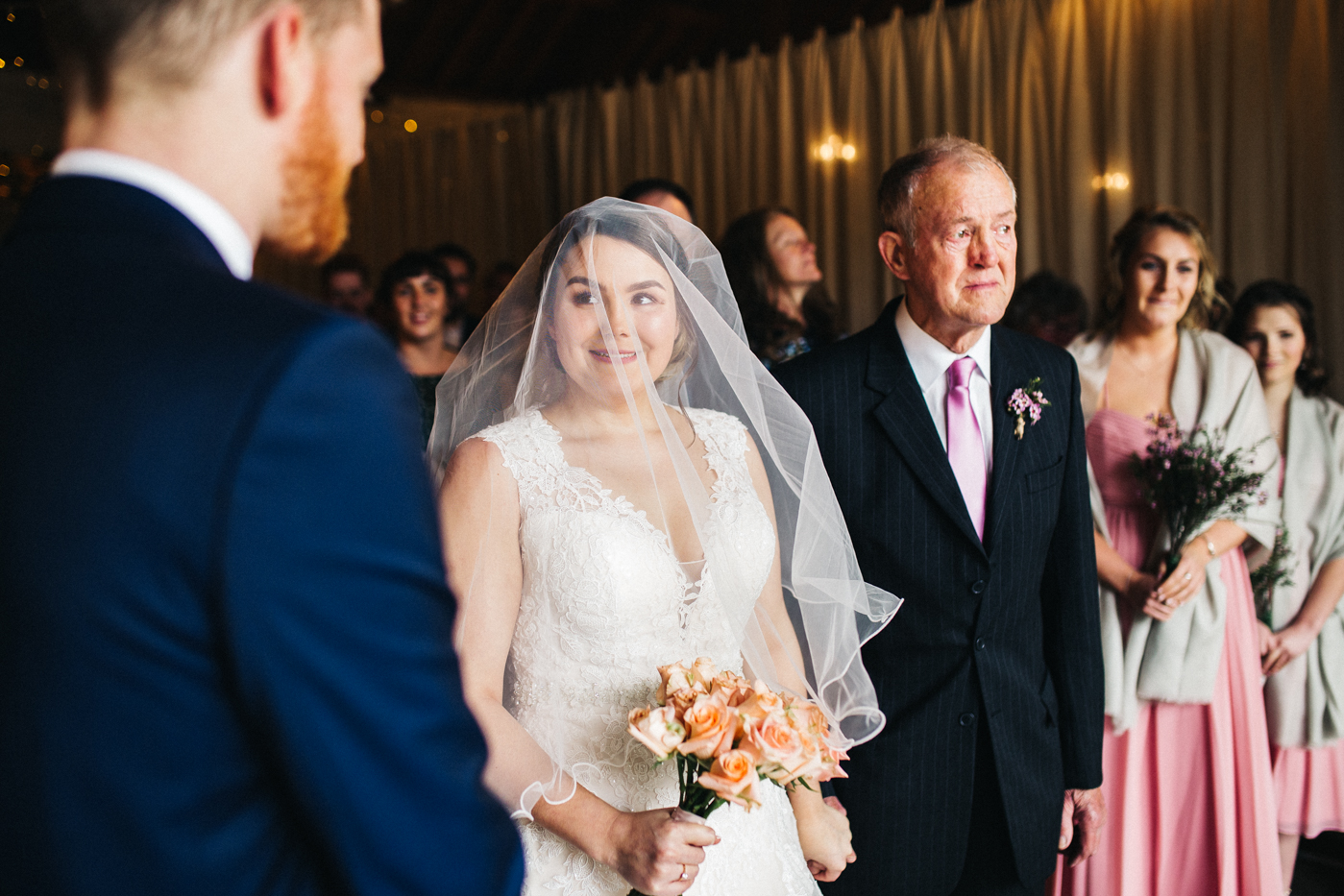 the bride smiles at the groom at the bottom of the aisle. spring barn wedding at east riddlesden hall keighley west yorkshire wedding photographer