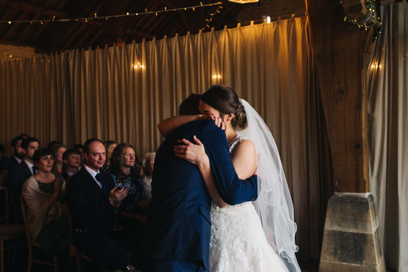 the bride and groom hug during the ceremony. spring barn wedding at east riddlesden hall keighley west yorkshire wedding photographer