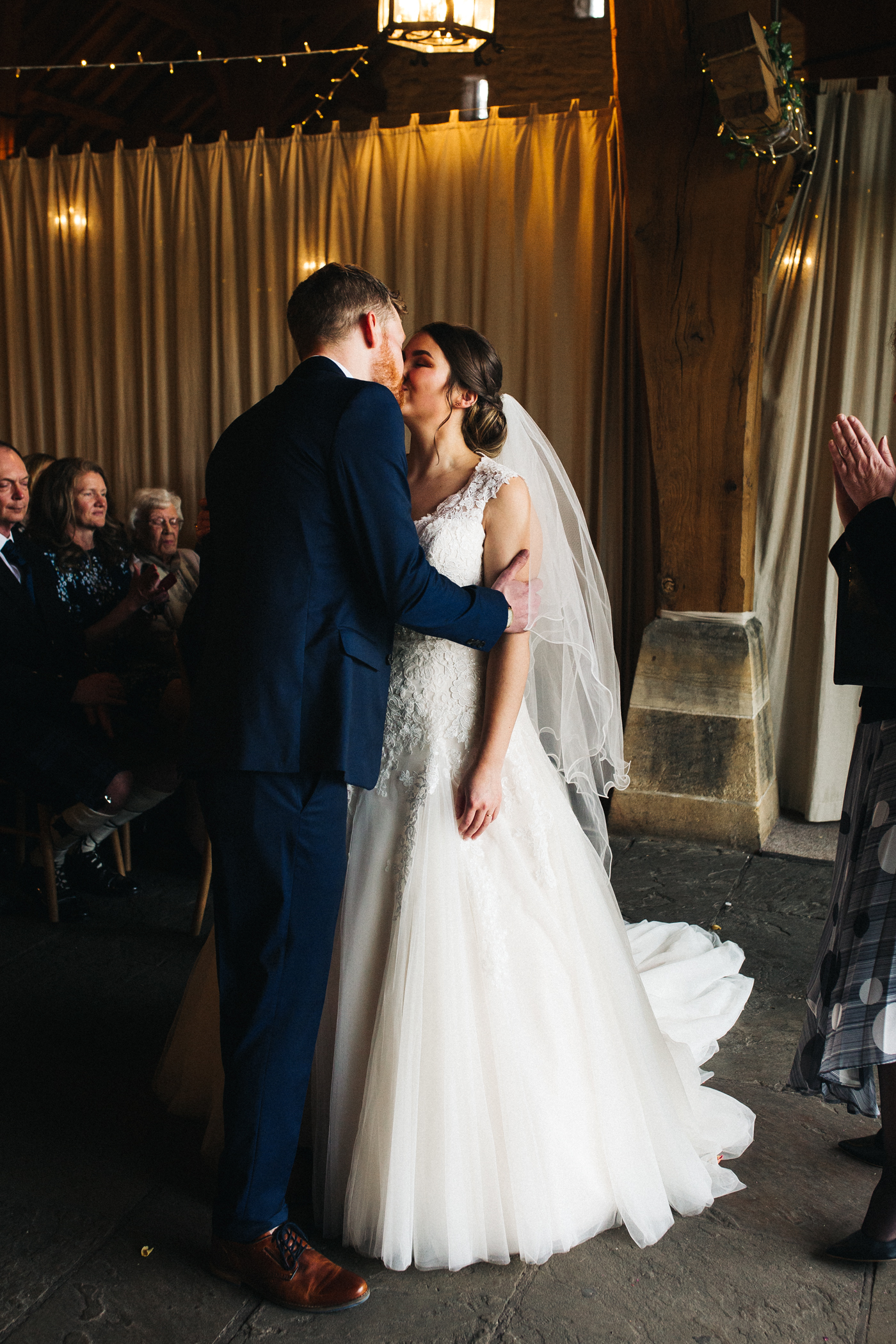 the bride and groom kiss during the ceremony. spring barn wedding at east riddlesden hall keighley west yorkshire wedding photographer