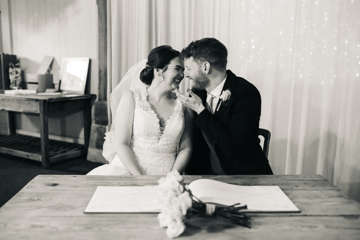 the bride and groom laugh during the register signing. spring barn wedding at east riddlesden hall keighley west yorkshire wedding photographer