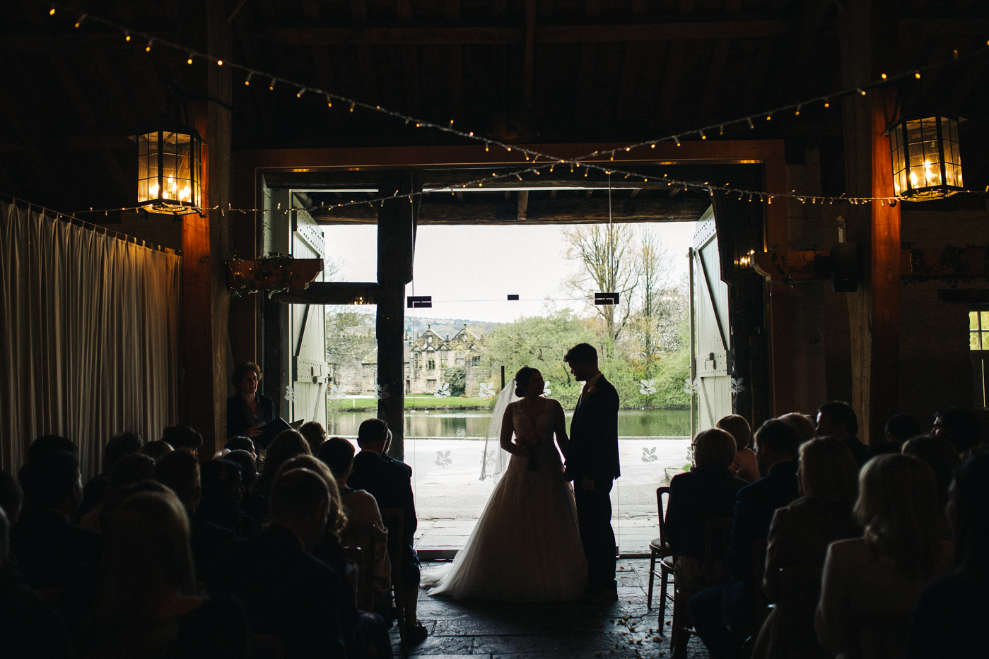 a wide shot of the bride and groom during the ceremony. spring barn wedding at east riddlesden hall keighley west yorkshire wedding photographer