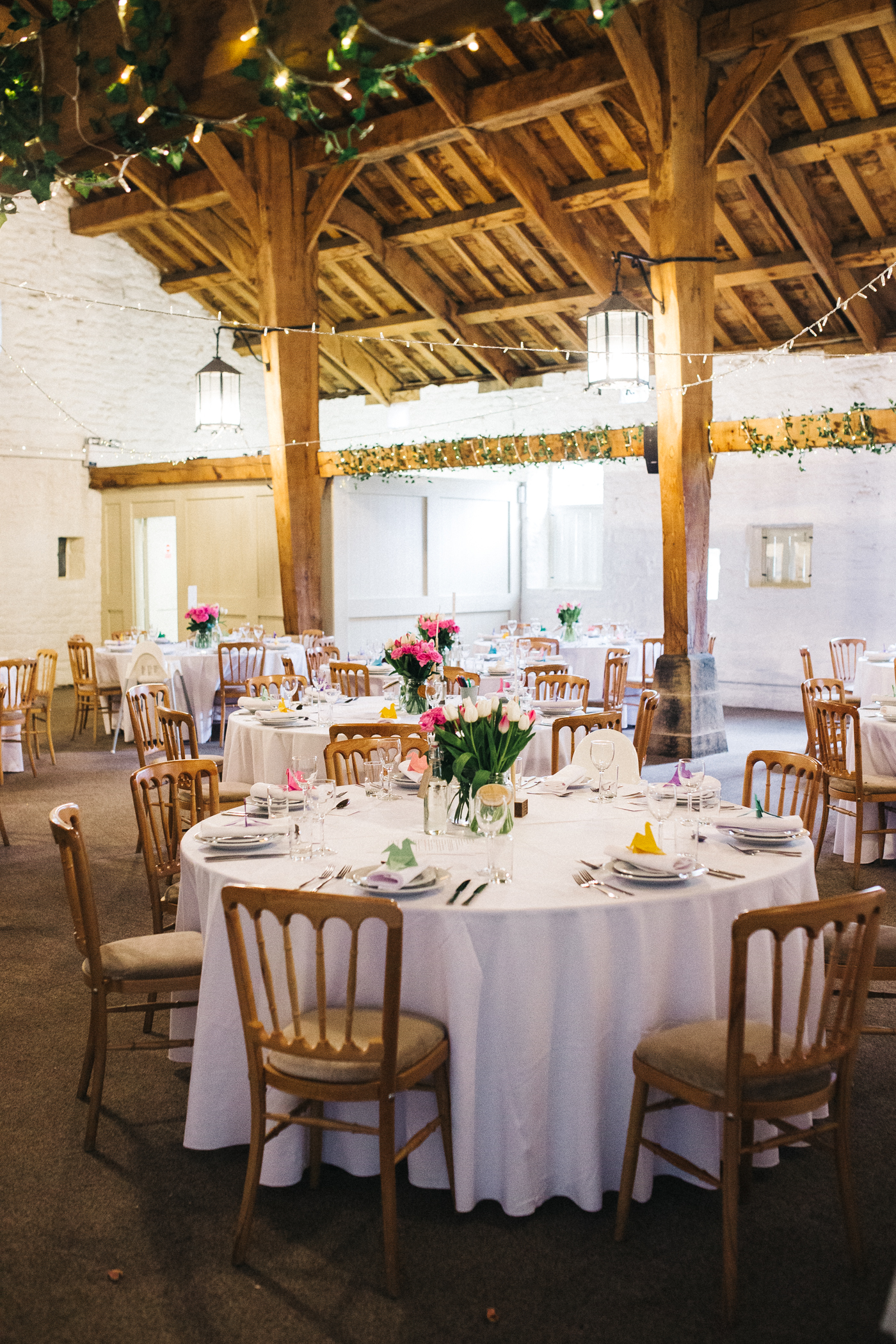 the barn is decorated for a spring wedding with tulips. spring barn wedding at east riddlesden hall keighley west yorkshire wedding photographer