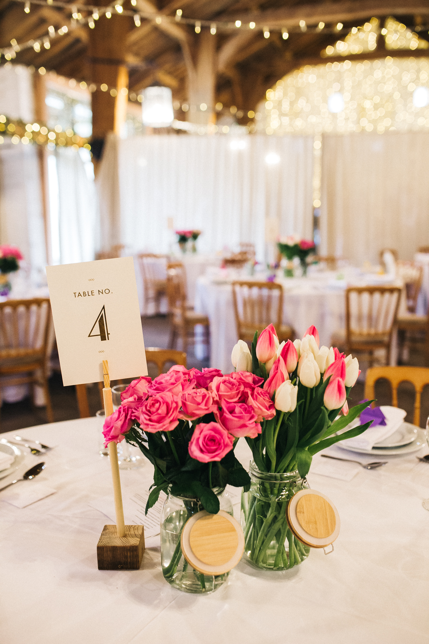 tulips and roses on the wedding tables. spring barn wedding at east riddlesden hall keighley west yorkshire wedding photographer
