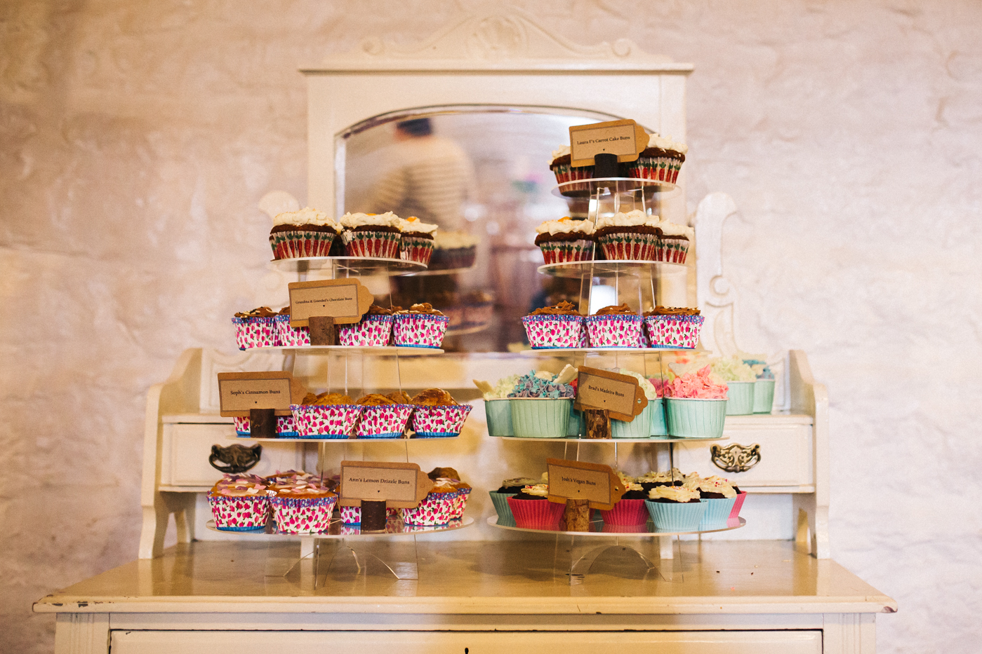 cupcakes piled high on a dresser at the wedding. spring barn wedding at east riddlesden hall keighley west yorkshire wedding photographer