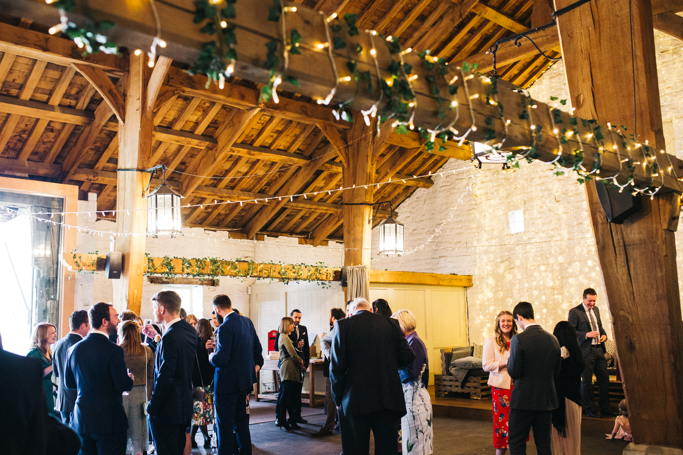 a wide shot of guests in the barn. spring barn wedding at east riddlesden hall keighley west yorkshire wedding photographer