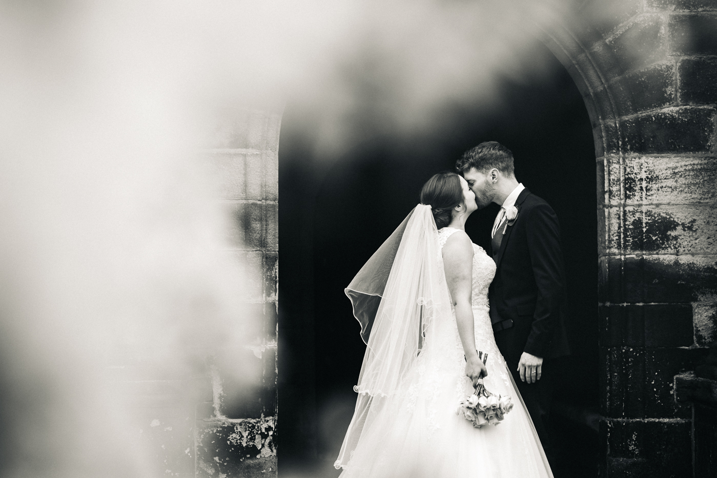 a black and white shot of the bride and groom kissing.spring barn wedding at east riddlesden hall keighley west yorkshire wedding photographer