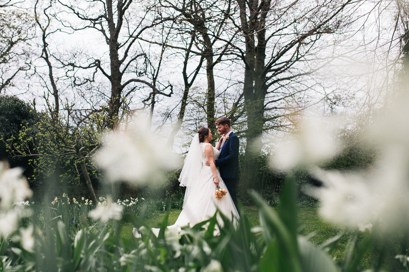 a wide shot of the bride and groom standing amongst flowers. spring barn wedding at east riddlesden hall keighley west yorkshire wedding photographer