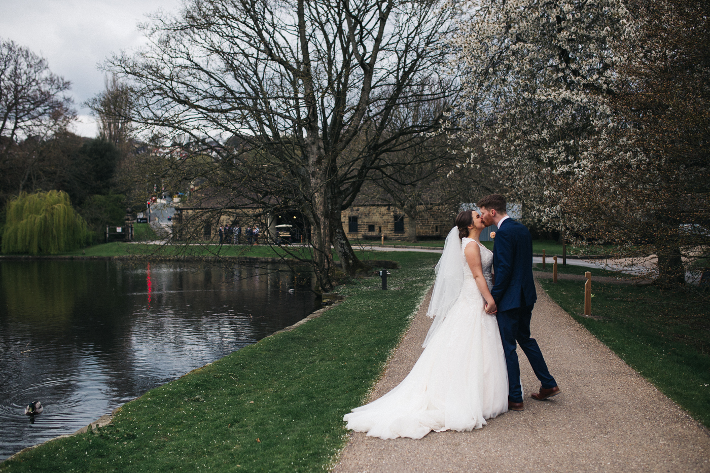 the bride and groom kiss walking along the lake. spring barn wedding at east riddlesden hall keighley west yorkshire wedding photographer