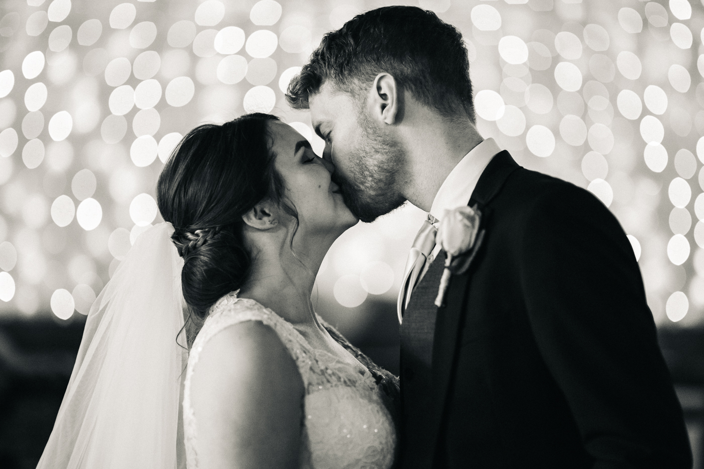 the bride and groom kiss in front of fairylights. spring barn wedding at east riddlesden hall keighley west yorkshire wedding photographer