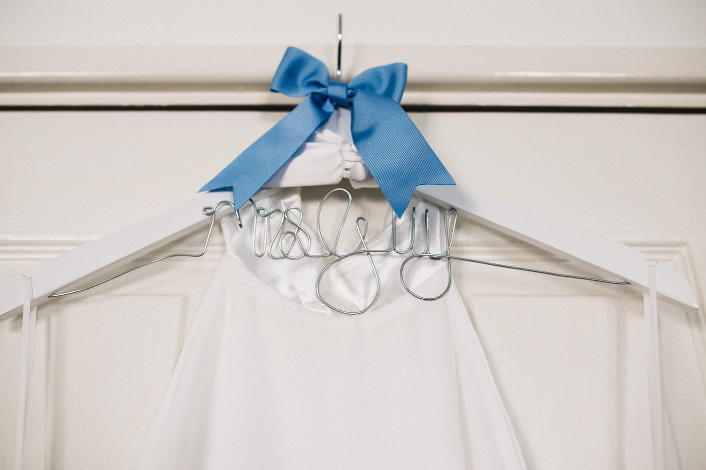 a edding dress hangs up with 'mrs guy' written on the coat hanger. relaxed teesside middlesbrough wedding photographer, wedding at home