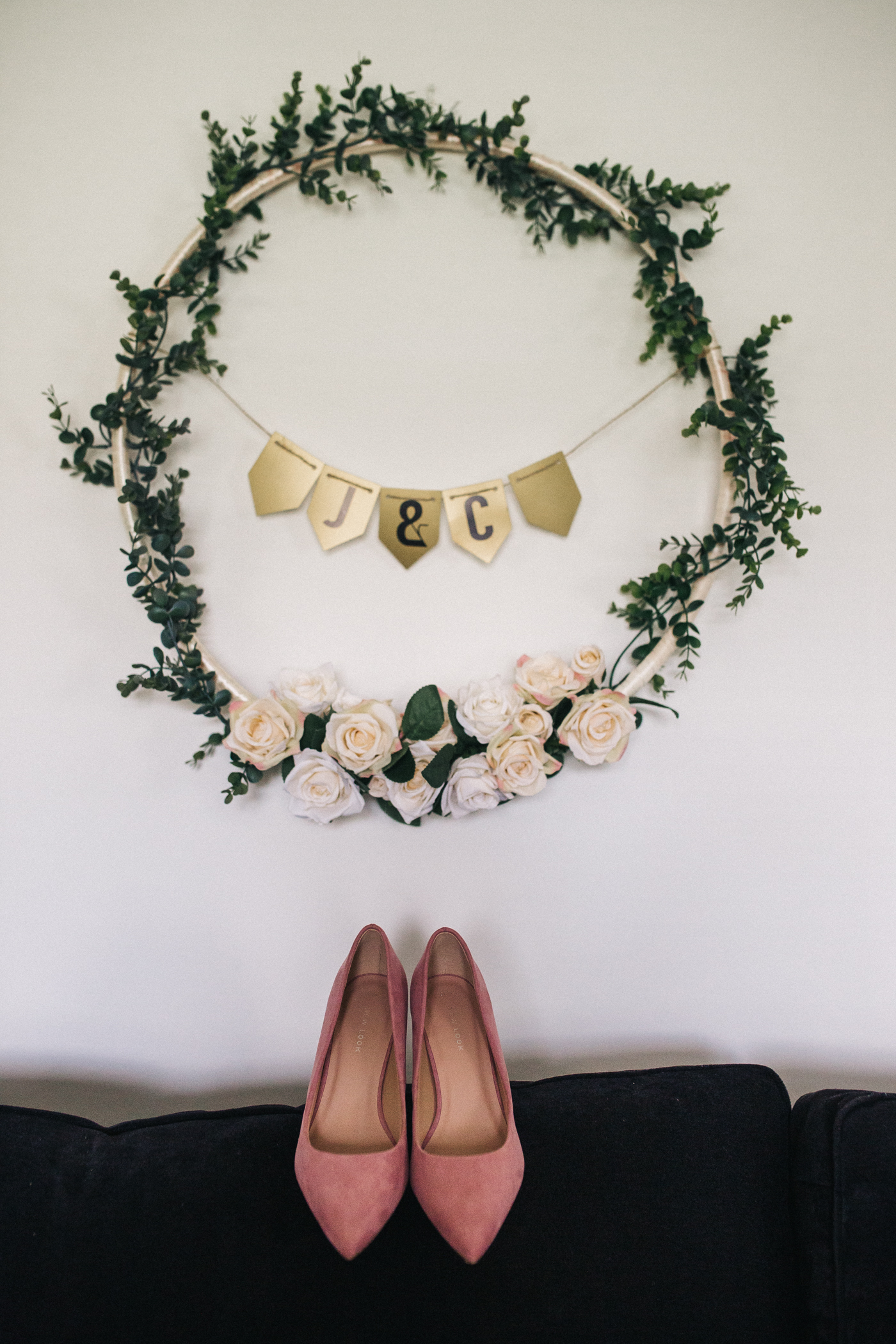pink wedding shoes and a wreath with flowers in the background. relaxed teesside middlesbrough wedding photographer, wedding at home