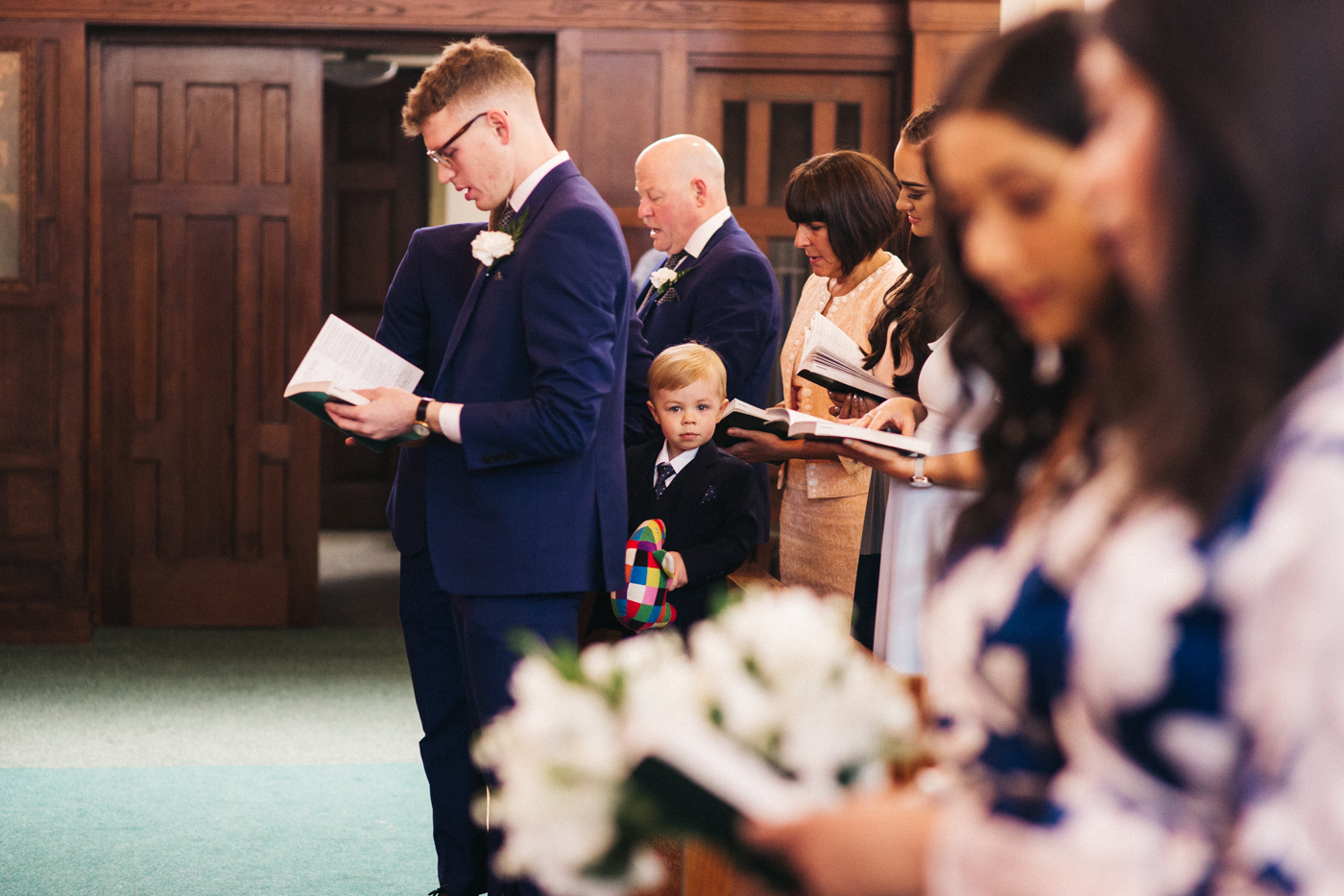 a little boy looks through the crowd at the church. relaxed teesside middlesbrough wedding photographer, wedding at home