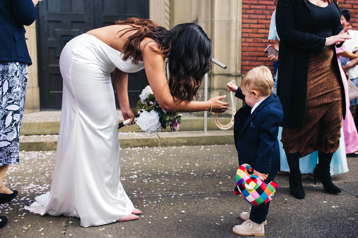 a little boy gives the bride a horseshoe. relaxed teesside middlesbrough wedding photographer, wedding at home