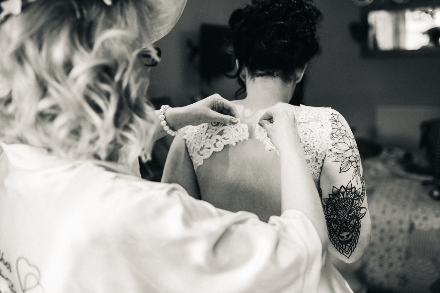 a bride has her lace dress done up. preston park museum wedding stockton teesside middlesbrough wedding photographer
