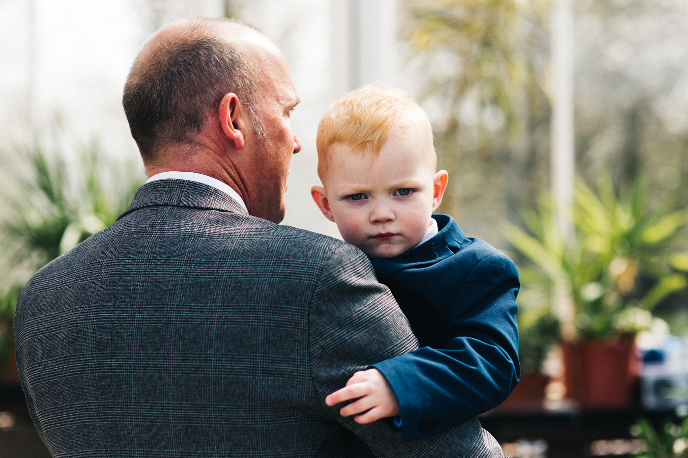a little boy is held and looks over his grandad's shoulder. preston park museum wedding stockton teesside middlesbrough wedding photographer