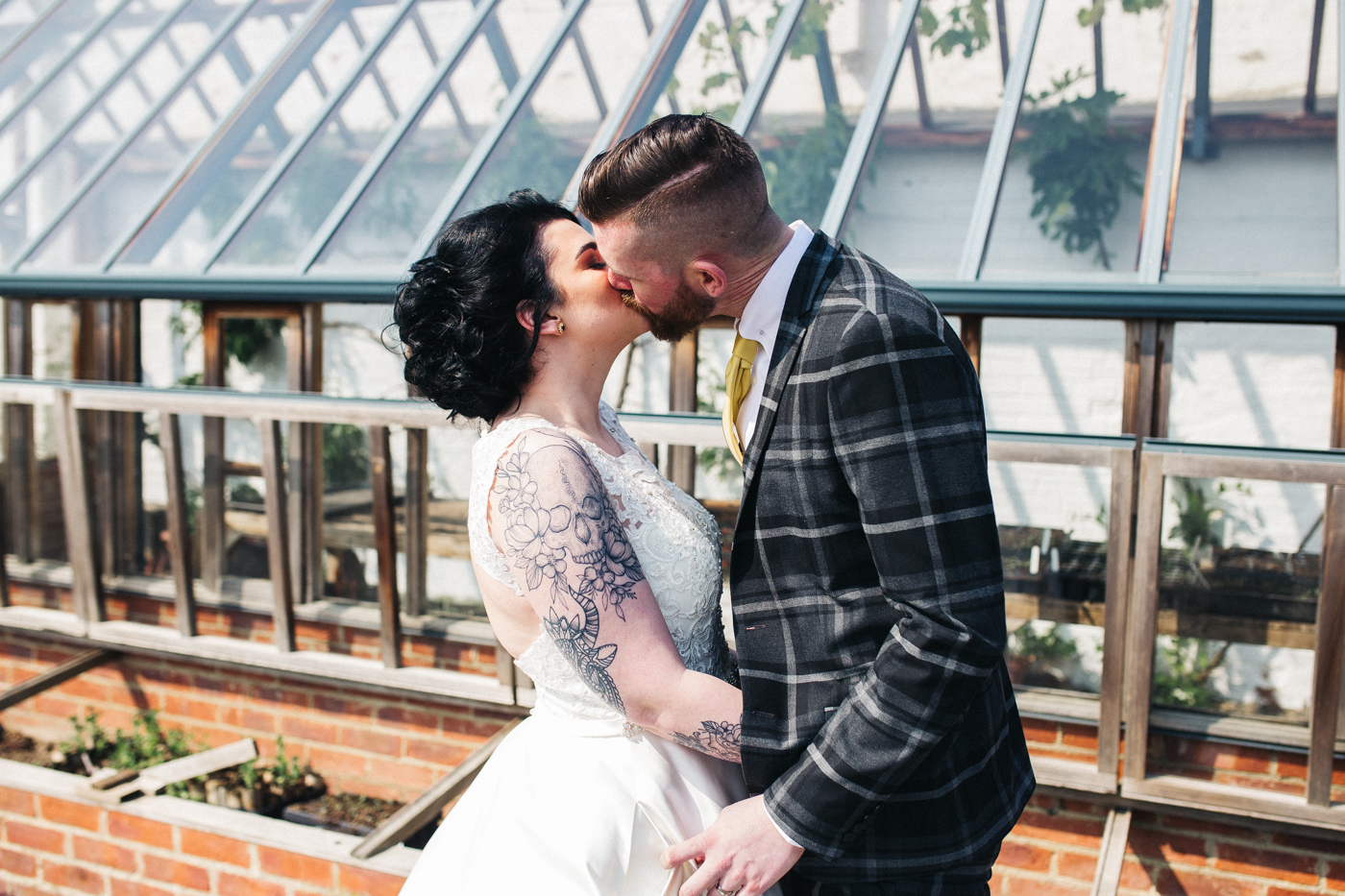 the bride and groom kiss in front of the victorian greenhouse. preston park museum wedding stockton teesside middlesbrough wedding photographer