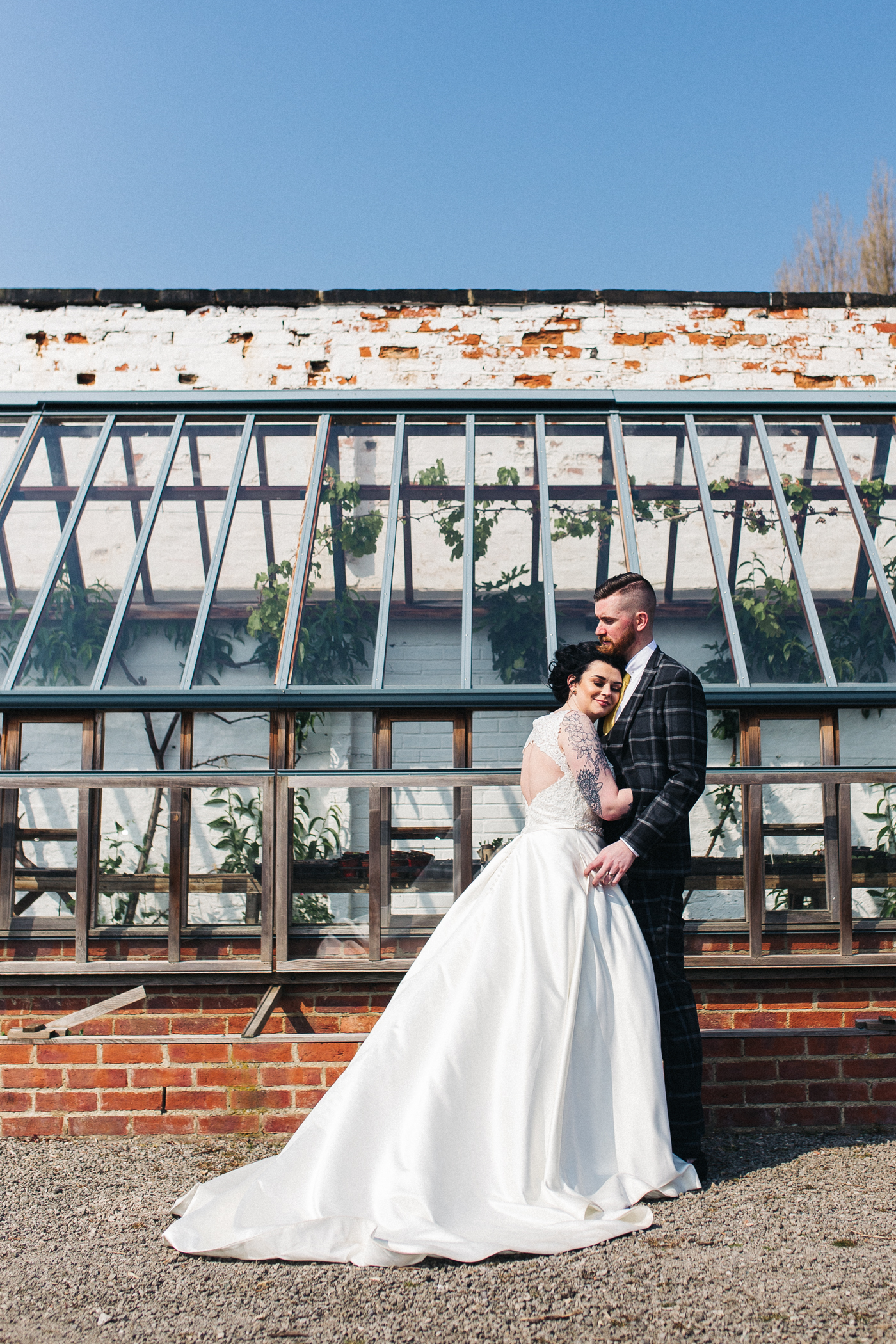 the bride and groom stand in front of a victorian greenhouse. preston park museum wedding stockton teesside middlesbrough wedding photographer