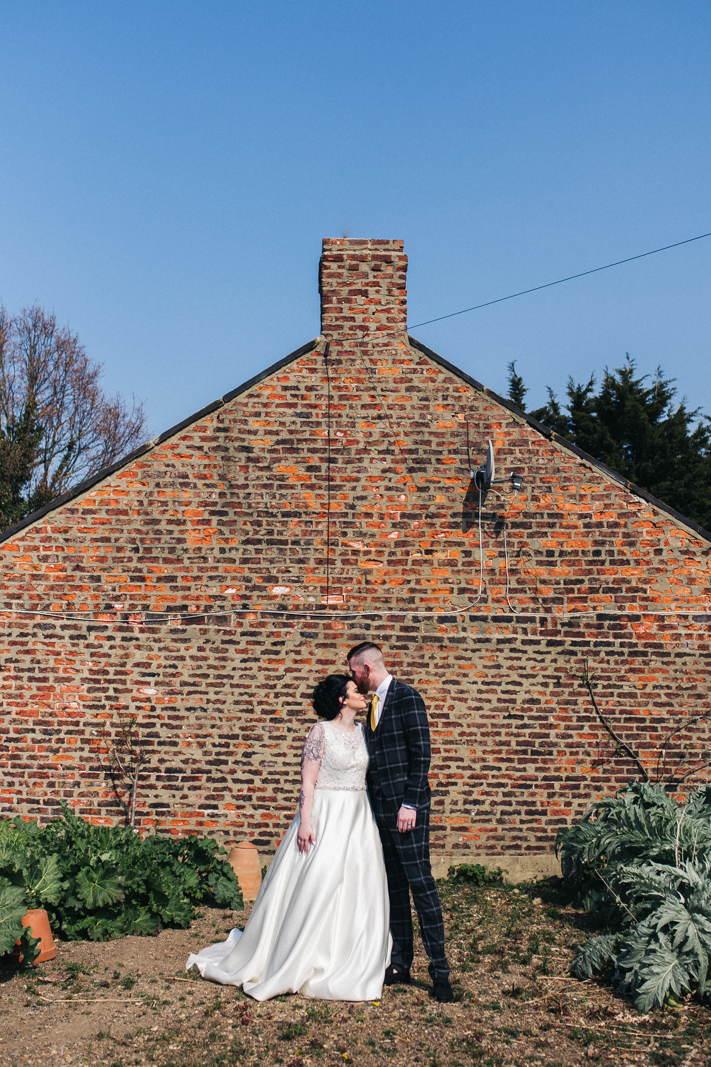 the bride and groom stand in allotments and look to each other. preston park museum wedding stockton teesside middlesbrough wedding photographer