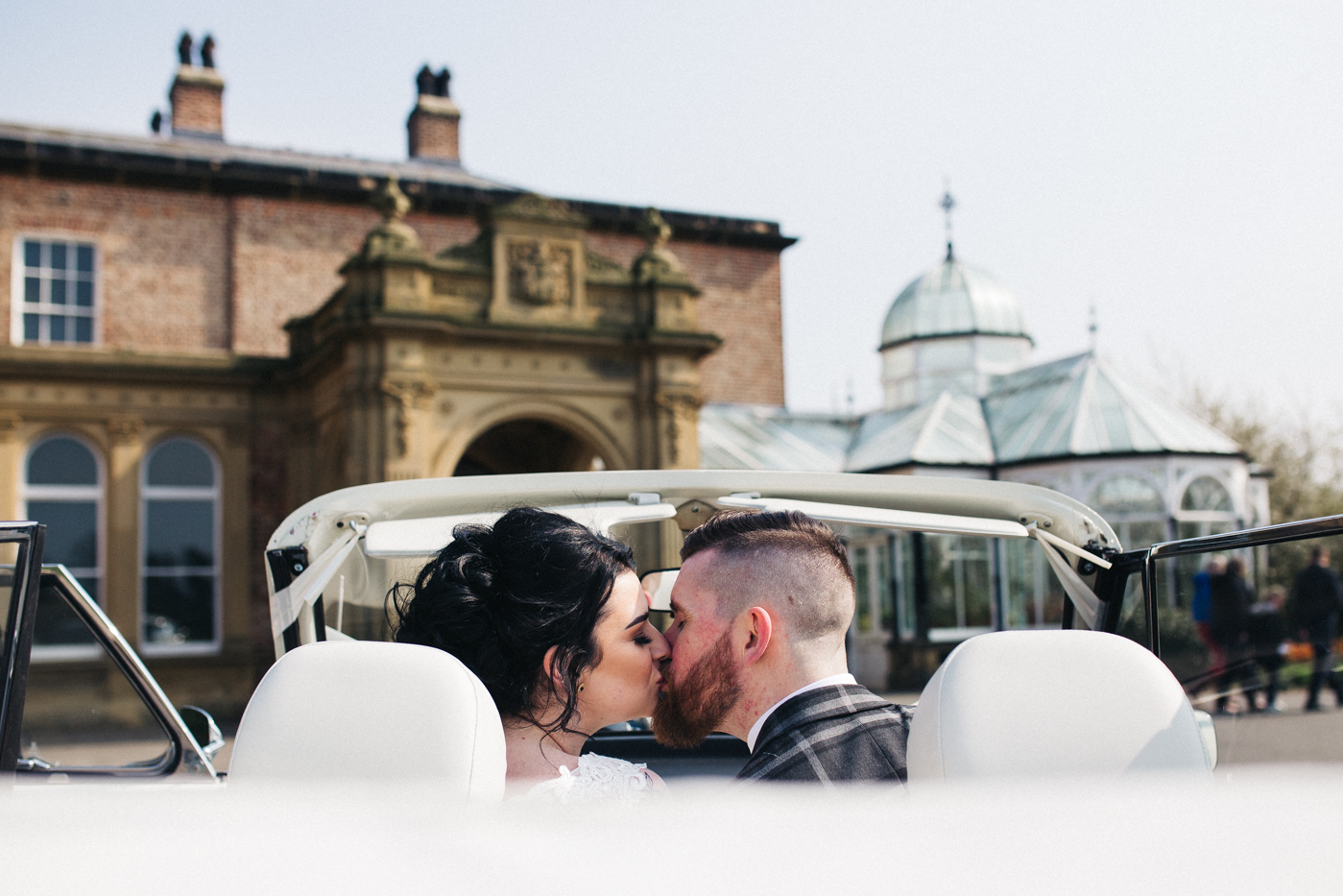 the bride and groom kiss in a car with the top down in front of their venue. preston park museum wedding stockton teesside middlesbrough wedding photographer