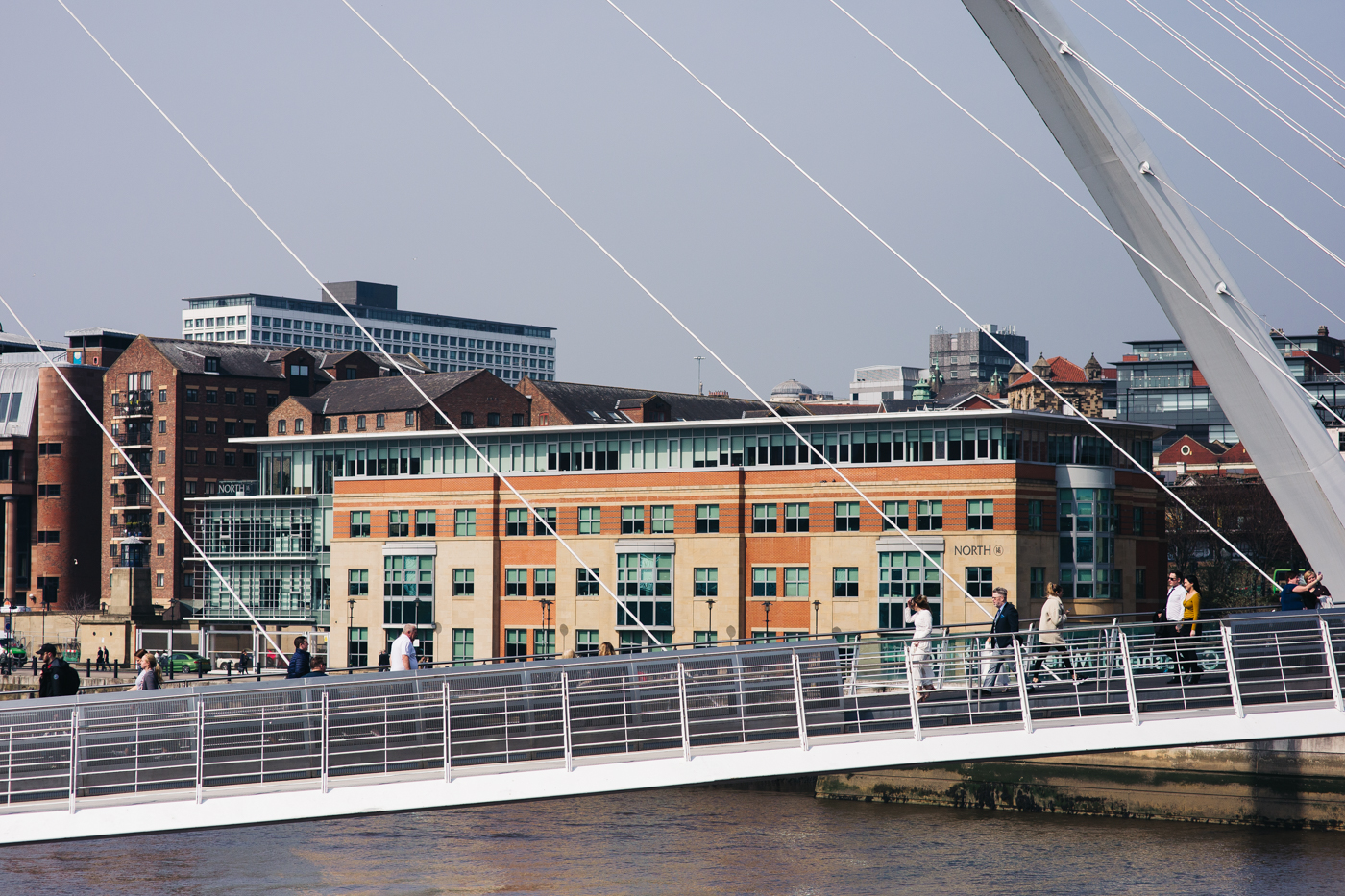 the bride walks over the bridge over the river tyne ahead of the ceremony. wedding at the baltic newcastle gateshead north east photographer
