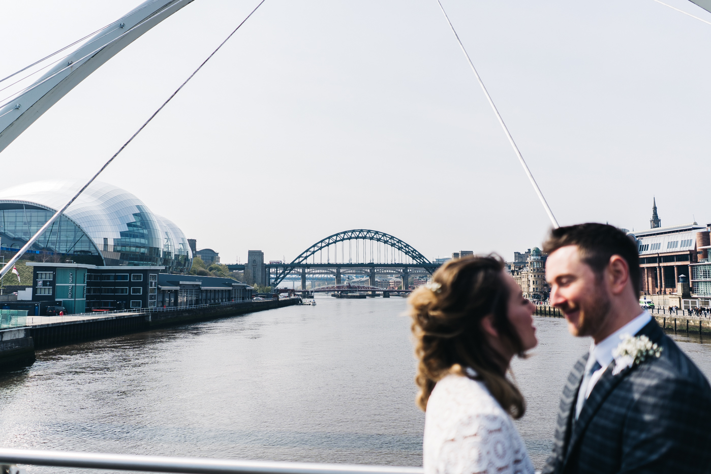 the couple stand closely with newcastle quayside in the background. wedding at the baltic newcastle gateshead north east photographer