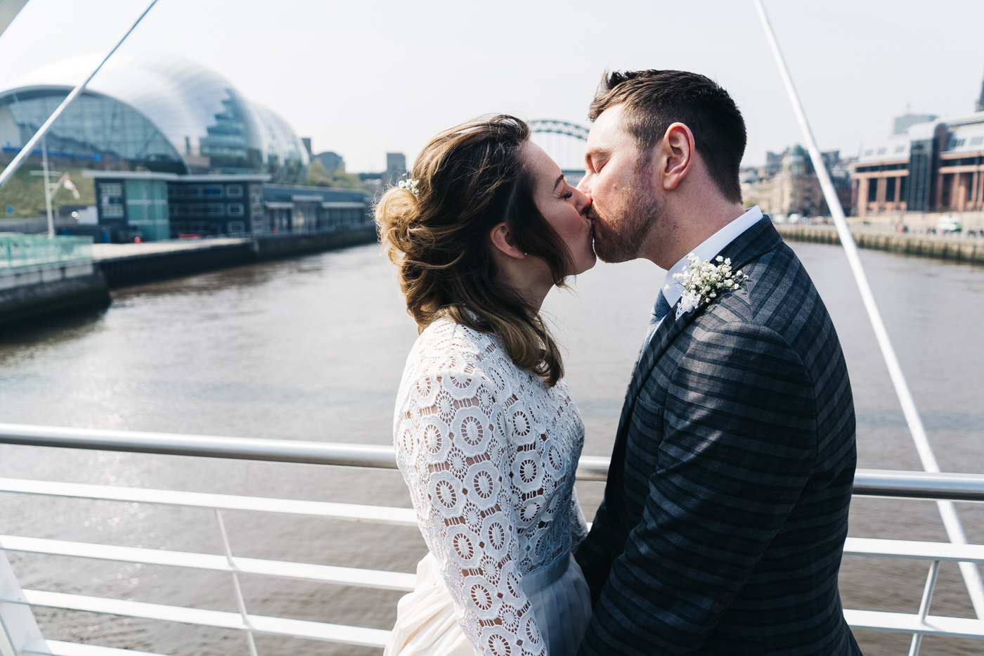 the couple kiss on the bride looking out over newcastle quayside. wedding at the baltic newcastle gateshead north east photographer