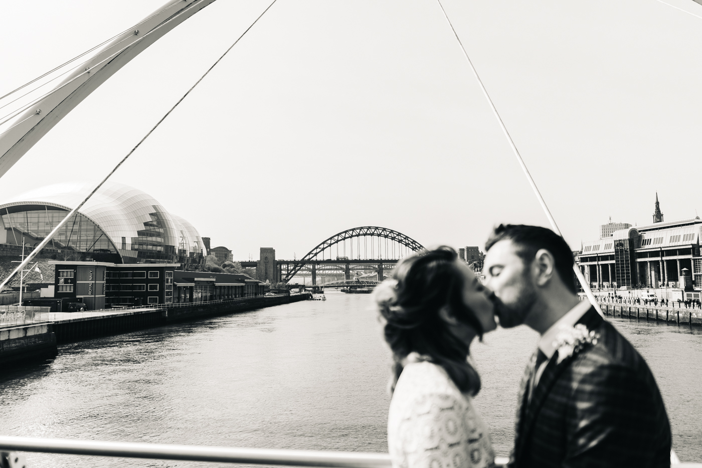 a black and white shot of the couple kissing on the bridge over the tyne river. wedding at the baltic newcastle gateshead north east photographer