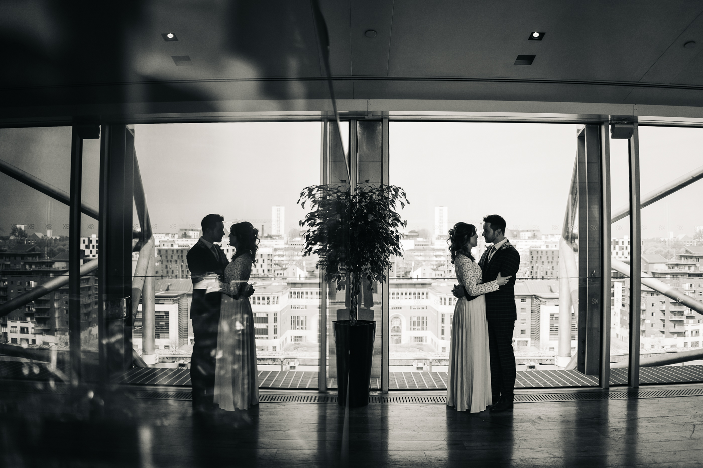 a reflection shot of the bride and groom standing by a window against the Newcastle skyline. wedding at the baltic newcastle gateshead north east photographer