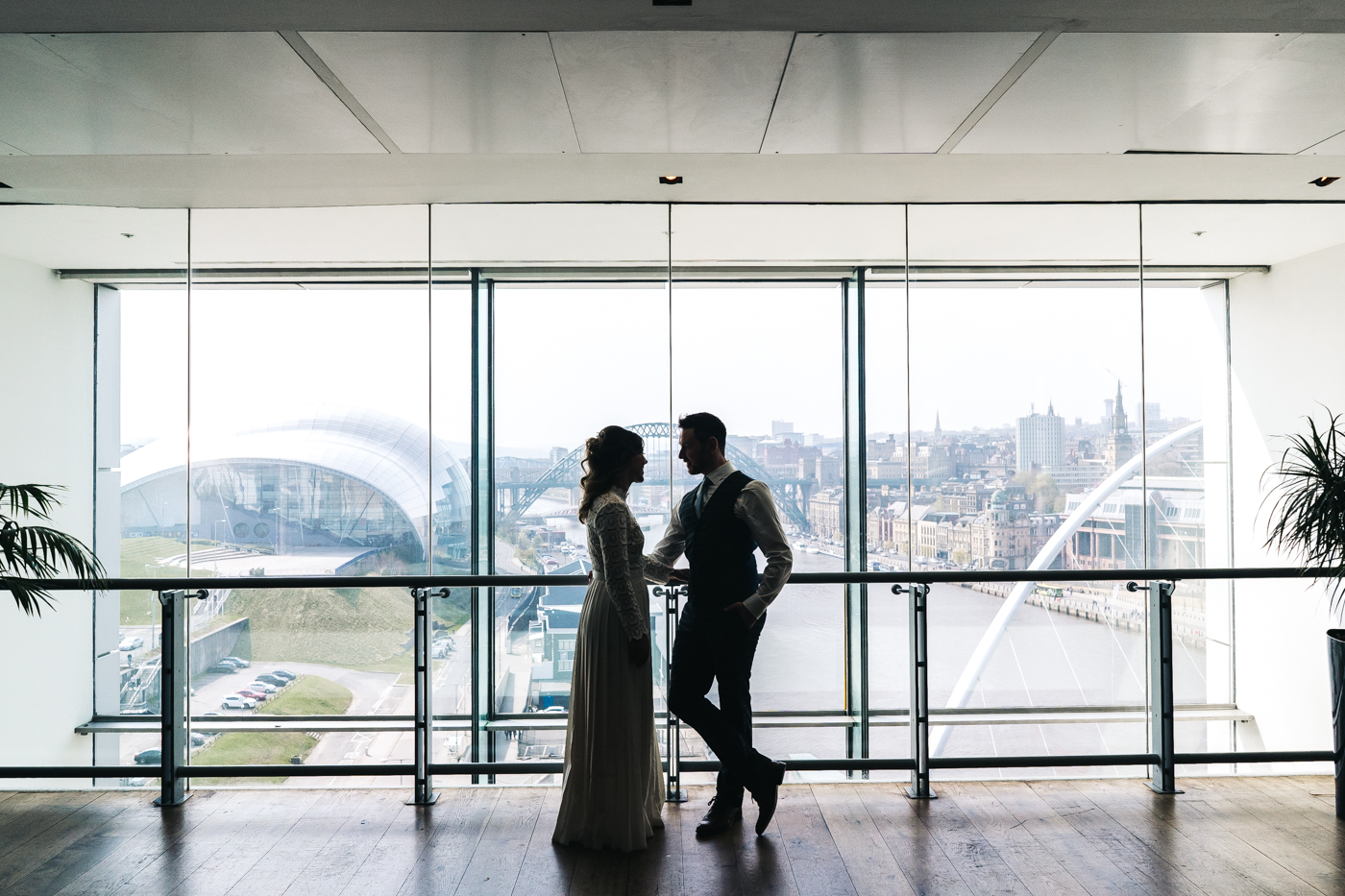 the bride and groom stand against a wide window with the newcastle quayside in the background. wedding at the baltic newcastle gateshead north east photographer