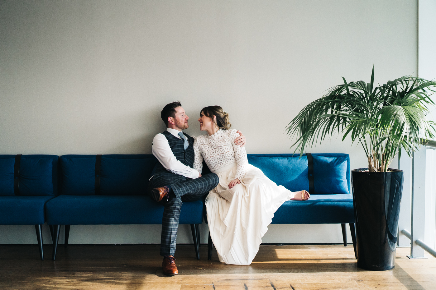 a wide shot of the couple sitting on a blue sofa together. wedding at the baltic newcastle gateshead north east photographer