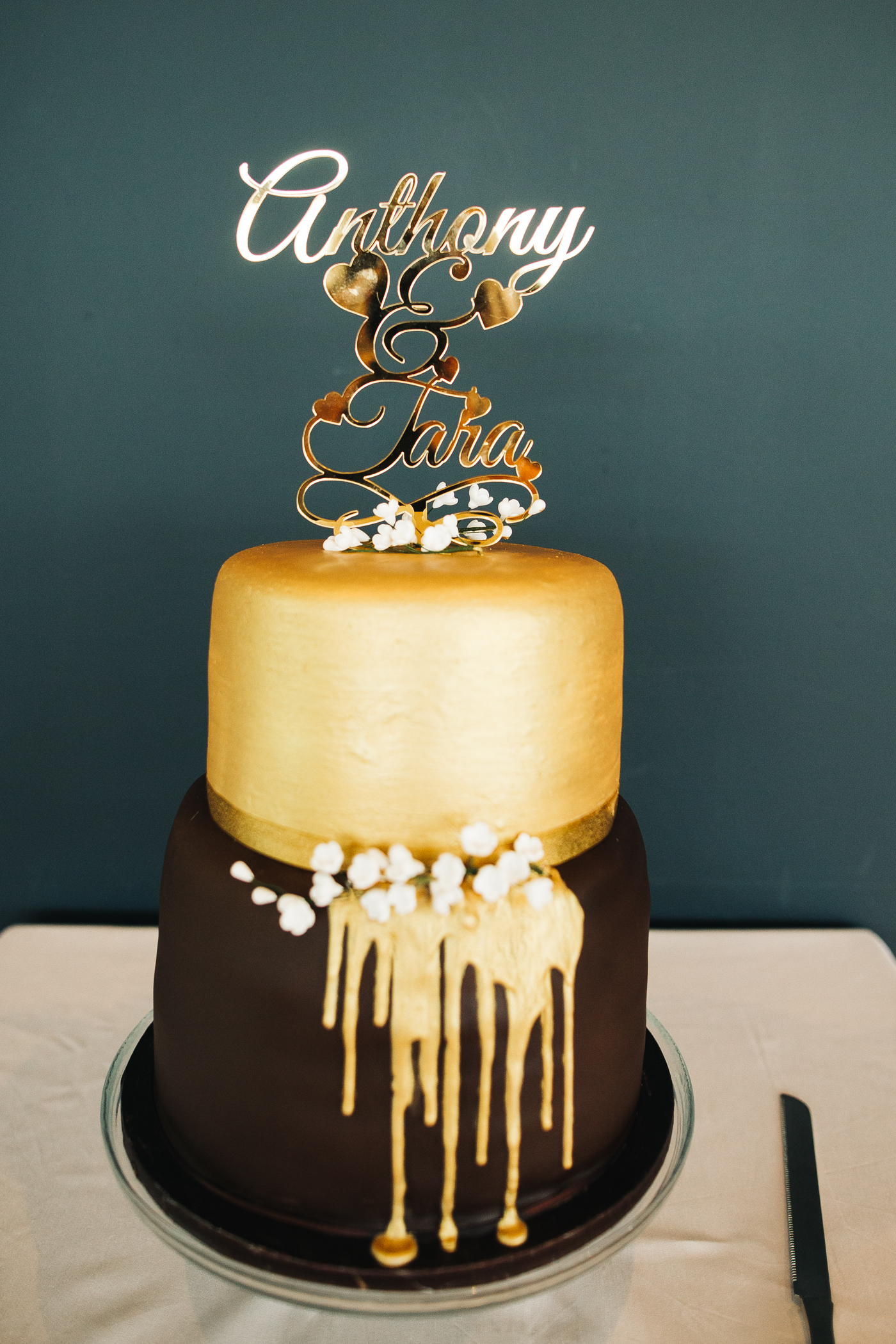 """a gold and chocolate cake with a cake topper reading 'anthony and tara"""". wedding at the baltic newcastle gateshead north east photographer"""