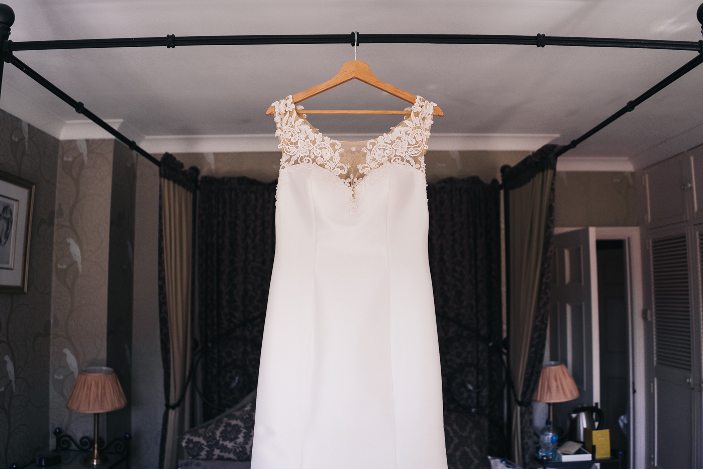 a wedding dress hung on the bed frame. wedding at laskill house north yorkshire helmsley wedding photographer north east teesside