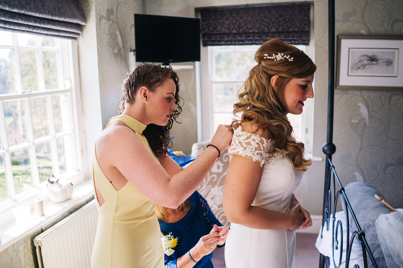 a bridesmaids fixes the bride's dress. wedding at laskill house north yorkshire helmsley wedding photographer north east teesside