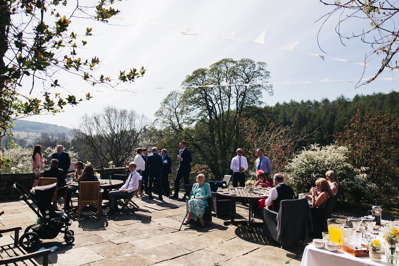 a wide shot of guests sitting in the sunshine in a courtyard. wedding at laskill house north yorkshire helmsley wedding photographer north east teesside