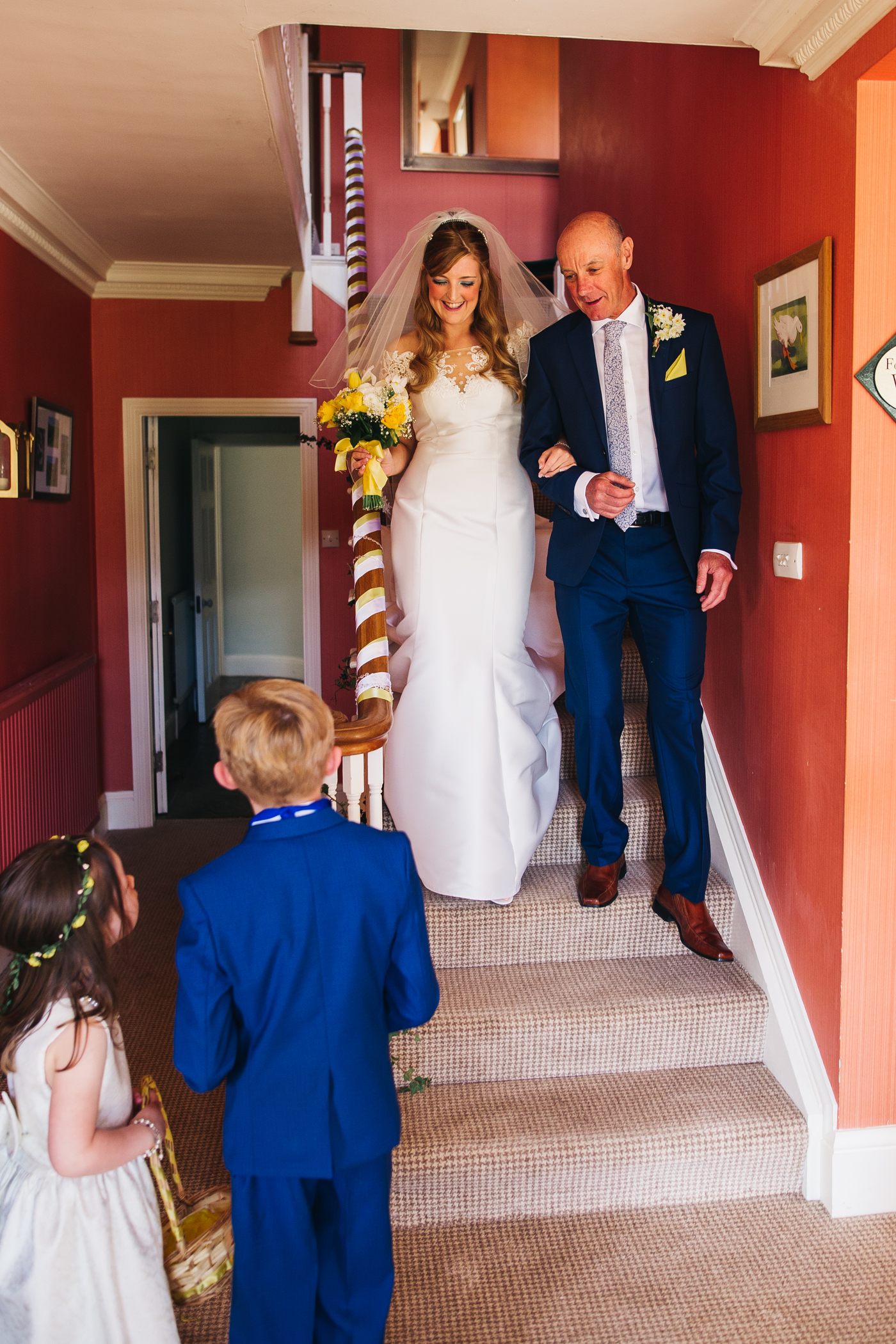 the bride and her dad come down the stairs and meet the page boy and flower girl. wedding at laskill house north yorkshire helmsley wedding photographer north east teesside
