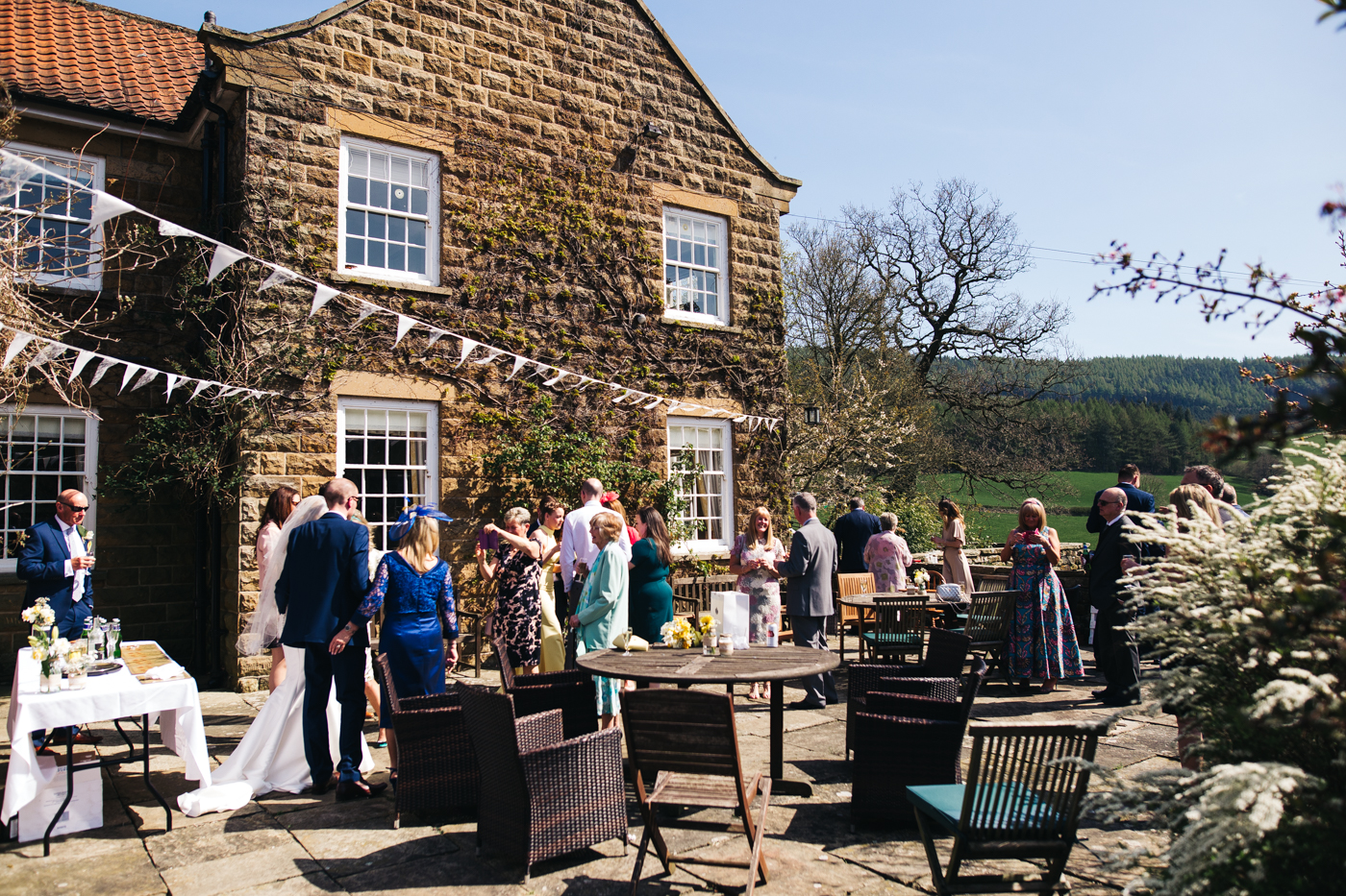 a wide shot of the couple and guests enjoying the sunshine in the courtyard. wedding at laskill house north yorkshire helmsley wedding photographer north east teesside