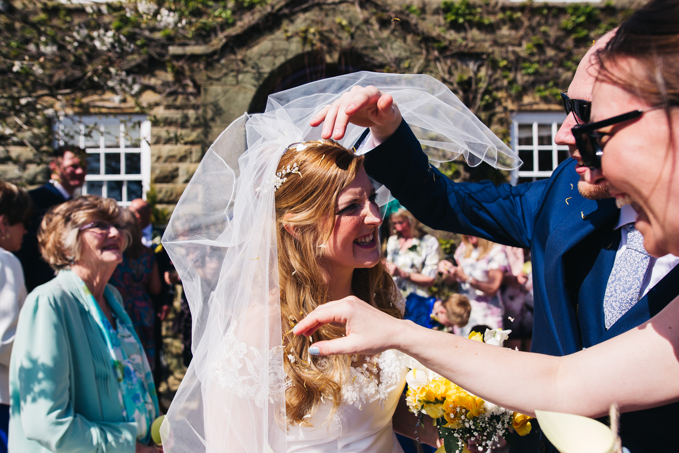 the groom and a guest pick confetti out of the bride's hair. wedding at laskill house north yorkshire helmsley wedding photographer north east teesside