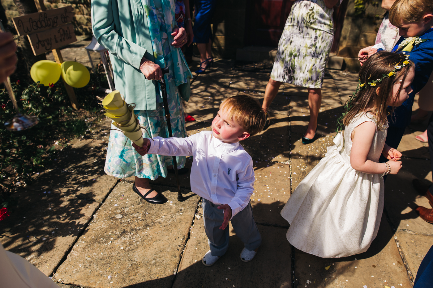 a young boy picks up and stacks used confetti cones. wedding at laskill house north yorkshire helmsley wedding photographer north east teesside