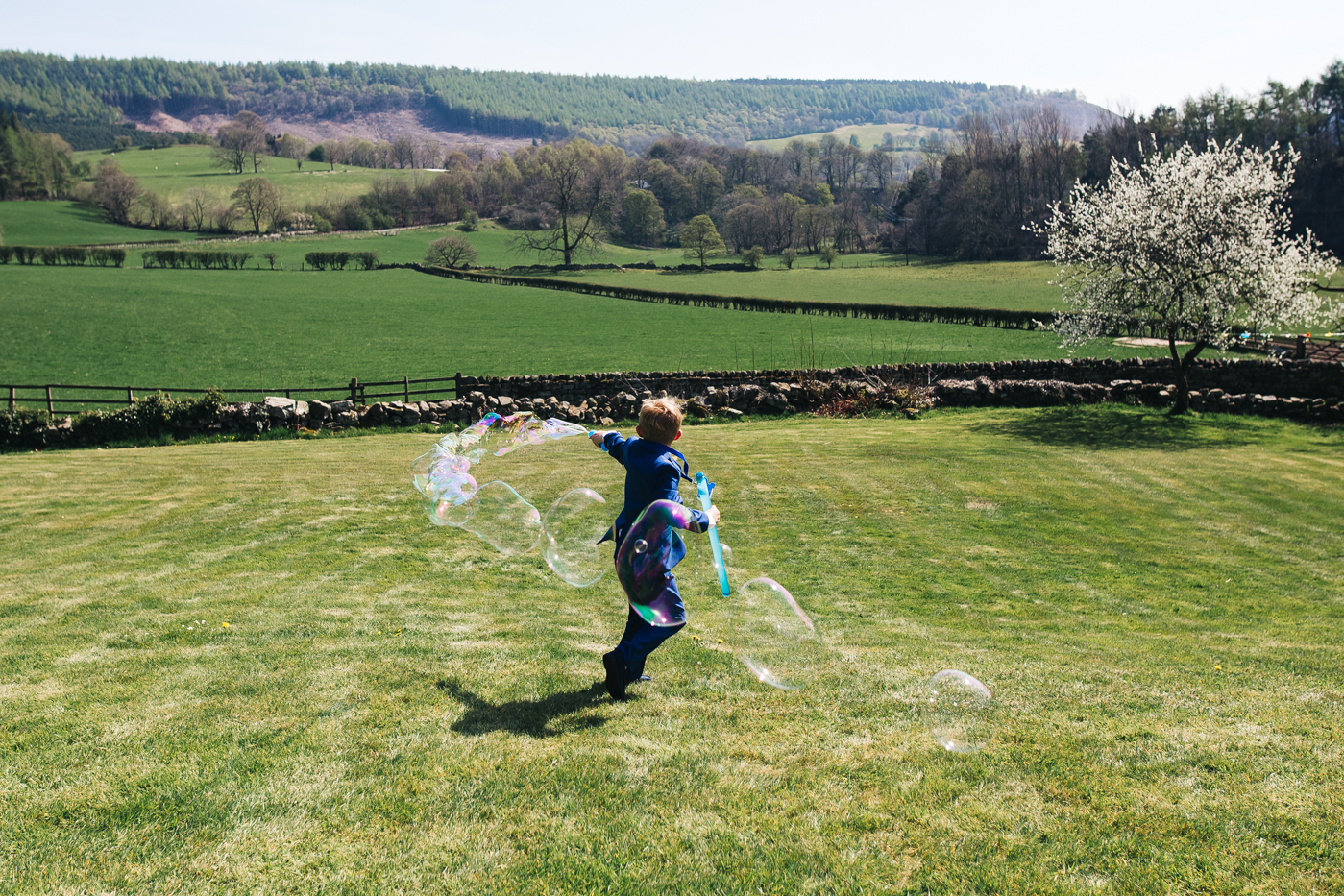a boy creates huge bubbles on the grass. wedding at laskill house north yorkshire helmsley wedding photographer north east teesside