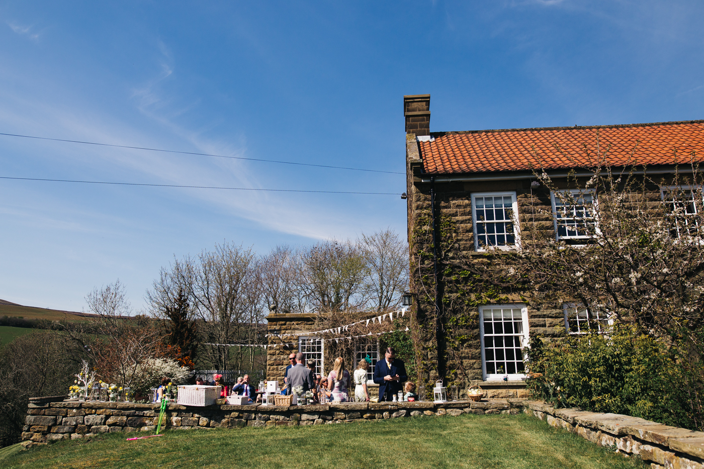 a wide shot of the house and guests mingling outside. wedding at laskill house north yorkshire helmsley wedding photographer north east teesside