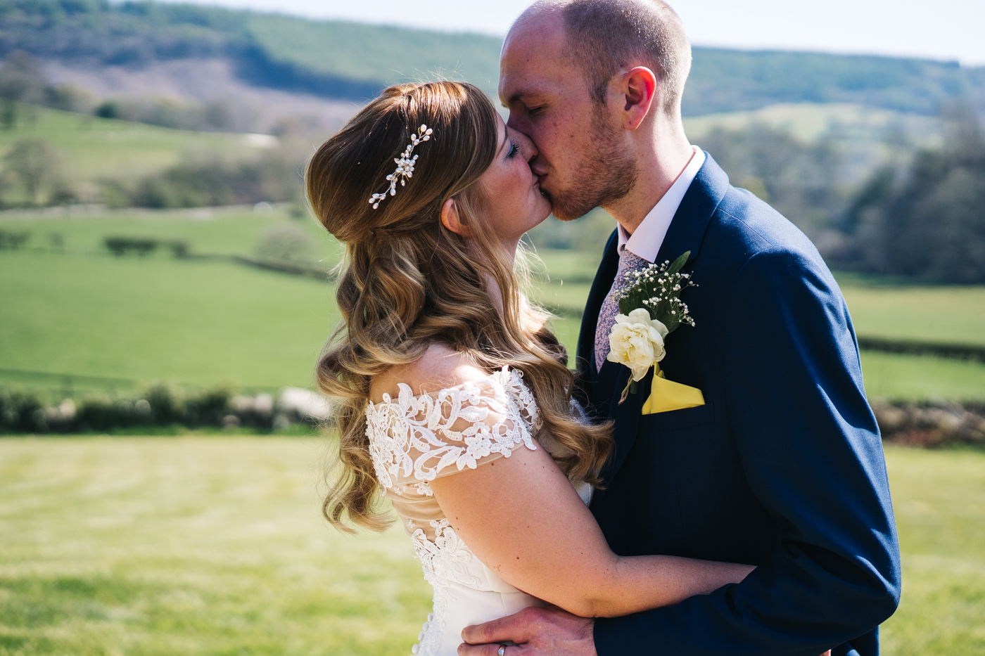 the couple kiss in front of a beautiful yorkshire view. wedding at laskill house north yorkshire helmsley wedding photographer north east teesside