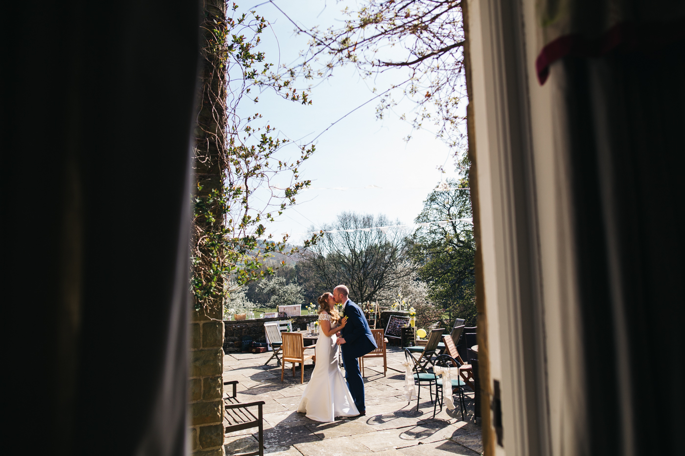 a wide shot of the courtyard with the couple standing and kissing. wedding at laskill house north yorkshire helmsley wedding photographer north east teesside