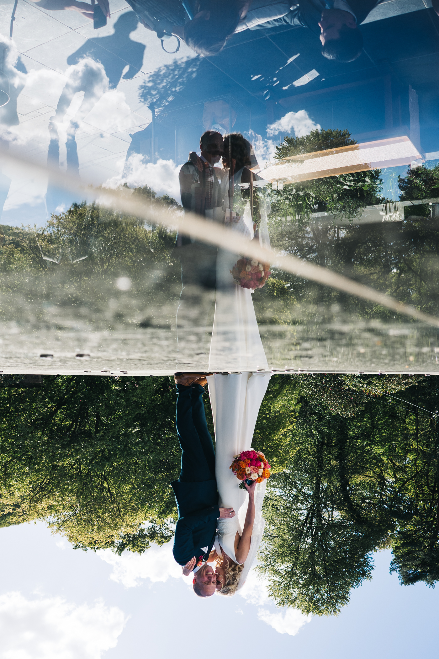 a reflection shot of a bride and groom standing on a glass roof. photo by sally t photography, wedding at ever after, devon, photographer
