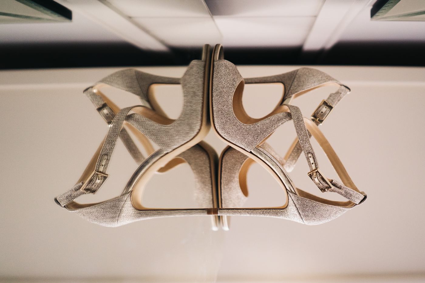 a reflection shot of gold jimmy choo wedding shoes on a mirrored table.  photo by sally t photography, wedding at ever after, tavistock, devon photographer